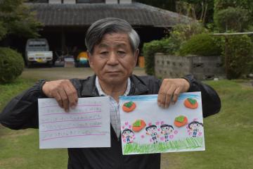 保育園児たちから寄せられた絵と手紙を手にする持丸正美さん=笠間市安居の自宅