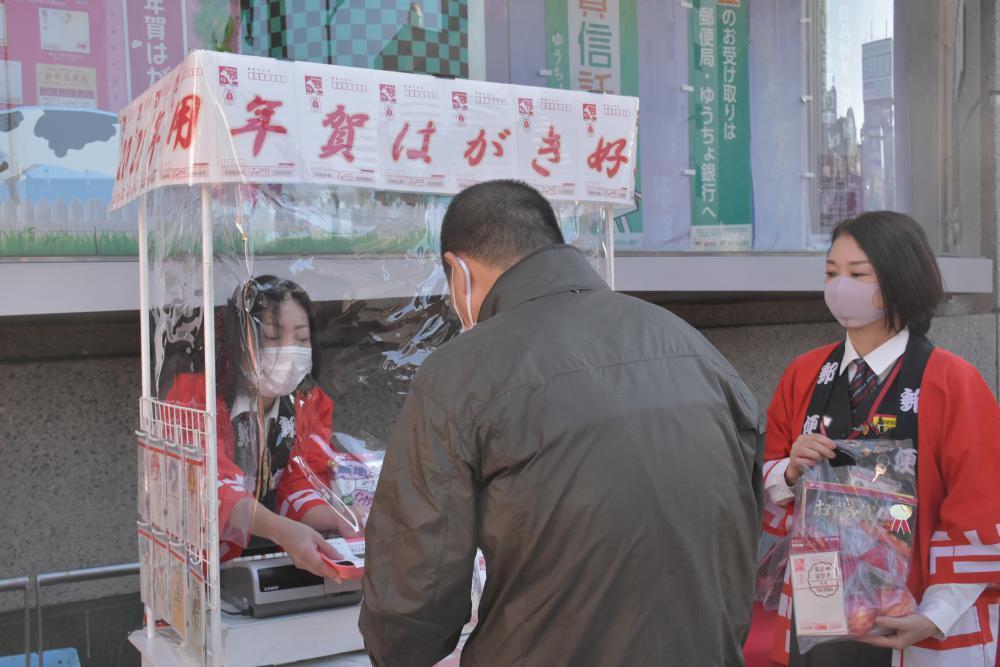 特設窓口で年賀はがきを買い求める男性=水戸市三の丸の水戸中央郵便局