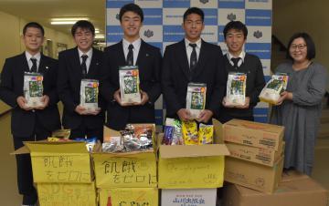 校内で呼び掛けた食料品を山内ゆかり代表(右)に寄付した茗渓学園の生徒=つくば市稲荷前