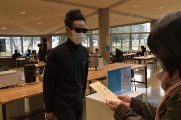 藝大食堂の「値段を付けないランチ」。支払う金額を明記した封筒をスタッフに渡す学生(中央)=取手市小文間の東京芸術大