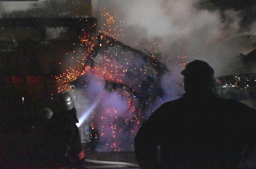 火花を散らして崩れる無量寿寺敷地内の建屋に放水する消防隊員ら=21日午後6時6分ごろ、鉾田市鳥栖