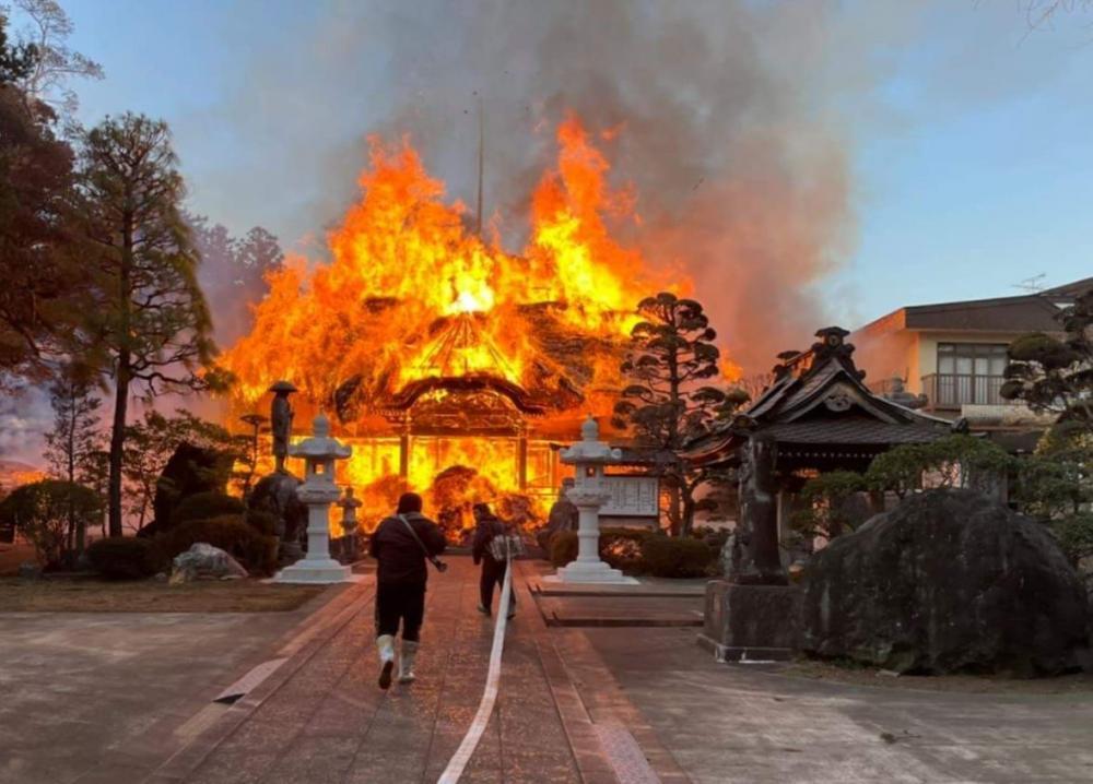 燃え上がる無量寿寺の本堂=21日午後4時ごろ(読者提供)