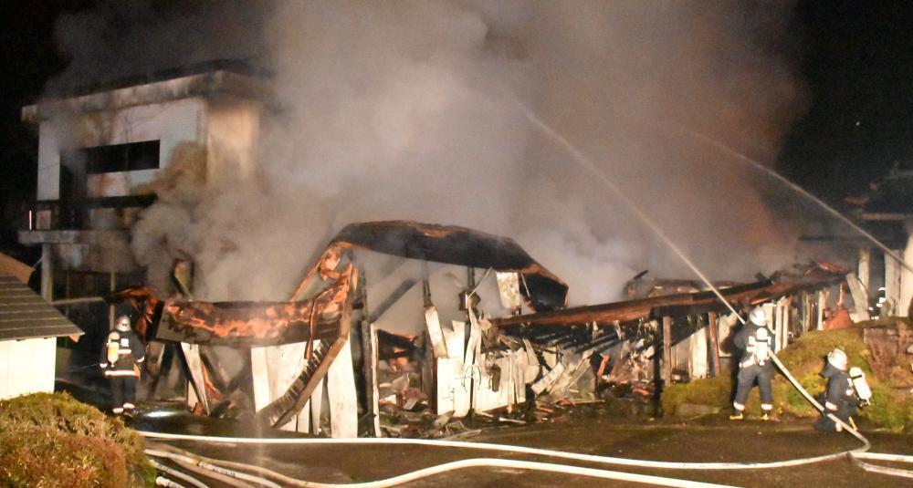 煙を上げて燃える無量寿寺敷地内の建屋に放水する消防隊員ら=21日午後6時6分ごろ、鉾田市鳥栖