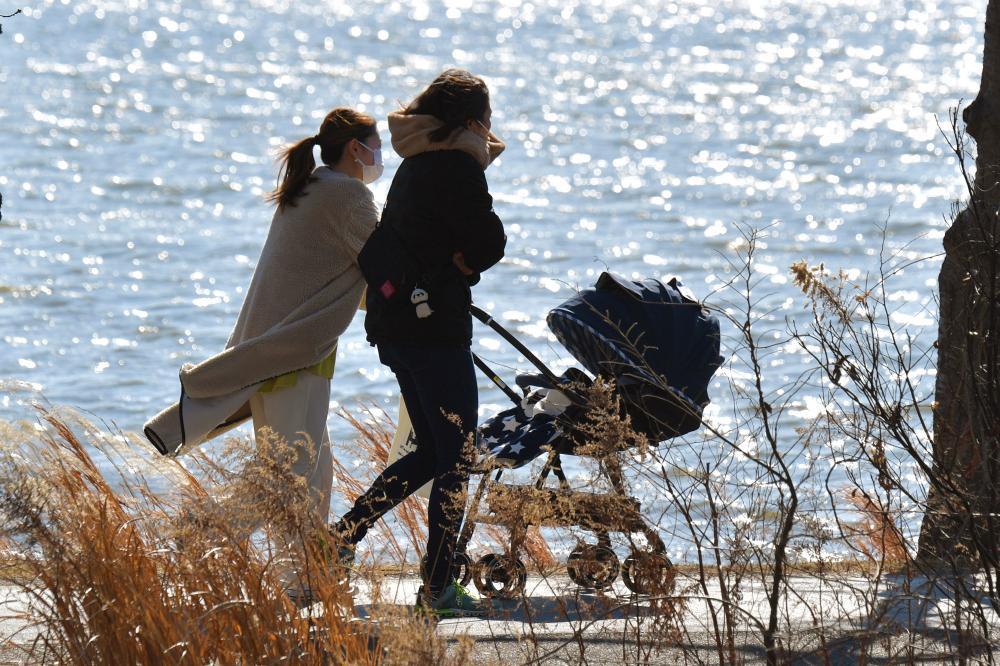 強風で波立つ千波湖のほとりを、上着をなびかせながら歩く女性たち=4日午後、水戸市千波町