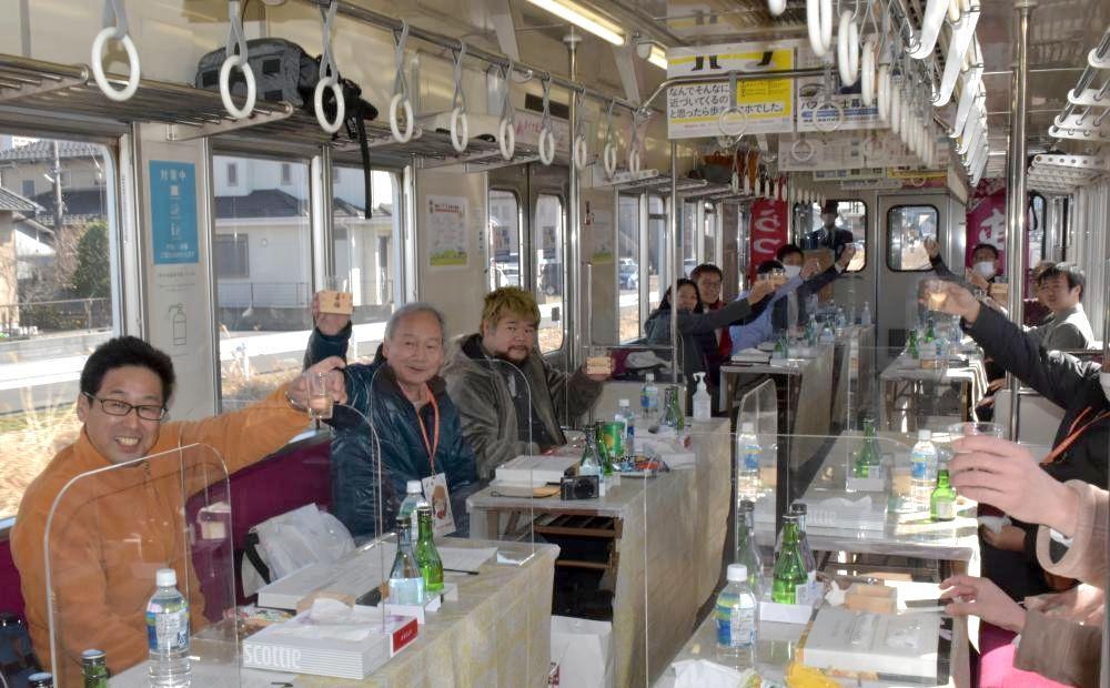 「日本酒列車」が出発し乾杯する参加者=関東鉄道常総線