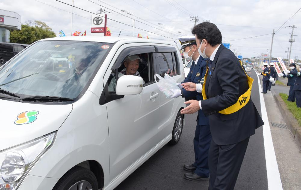 車の助手席に乗る人に交通安全啓発グッズを手渡す大部勝規高萩市長(右)と柴久喜康将高萩警察署長(右から2人目)=北茨城市関南町神岡下