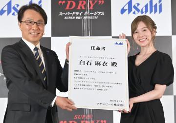 スーパードライミュージアムアンバサダーに就任し、松山一雄専務取締役(左)から任命書を受け取る白石麻衣さん=9日午後、守谷市緑