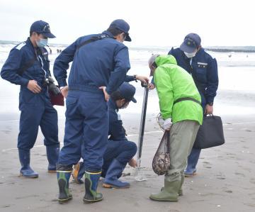 潮干狩り客が使用していた漁具の柄の長さを測る茨城海上保安部職員。県内では50センチ未満の漁具のみ使用が可能=4月中旬、大洗町大貫町の大洗サンビーチ