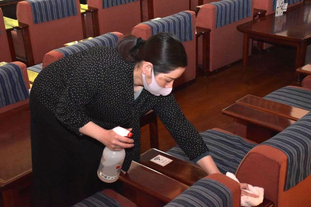 椅子の消毒作業をする旅館「筑波山江戸屋」の若おかみ=つくば市筑波