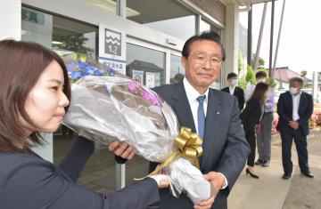 職員から花束を受け取る雑賀正光町長(右)=河内町役場