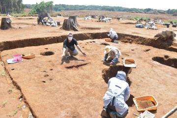 発掘調査員(左)が手を広げる赤茶色の場所には、古墳時代に使われた炉があったとされる=稲敷市上君山