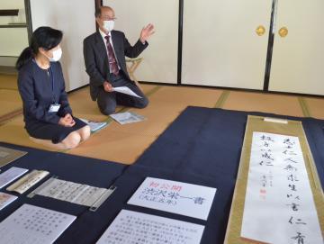 書と書簡について説明する所蔵者の後藤卓巳さん(右)と研究員の小圷のり子さん=水戸市三の丸