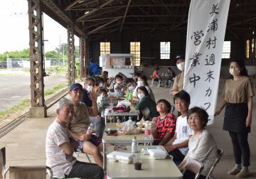 美浦村初の地域おこし協力隊として着任した村川さん夫婦(右)が、倉庫跡でキッチンカーによるカフェを始めた=美浦村大山