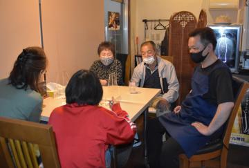 カレーを食べる子どもを見守るアイズカフェの石田健一さん(右)と民生委員の谷田部典子さん(左)=ひたちなか市表町