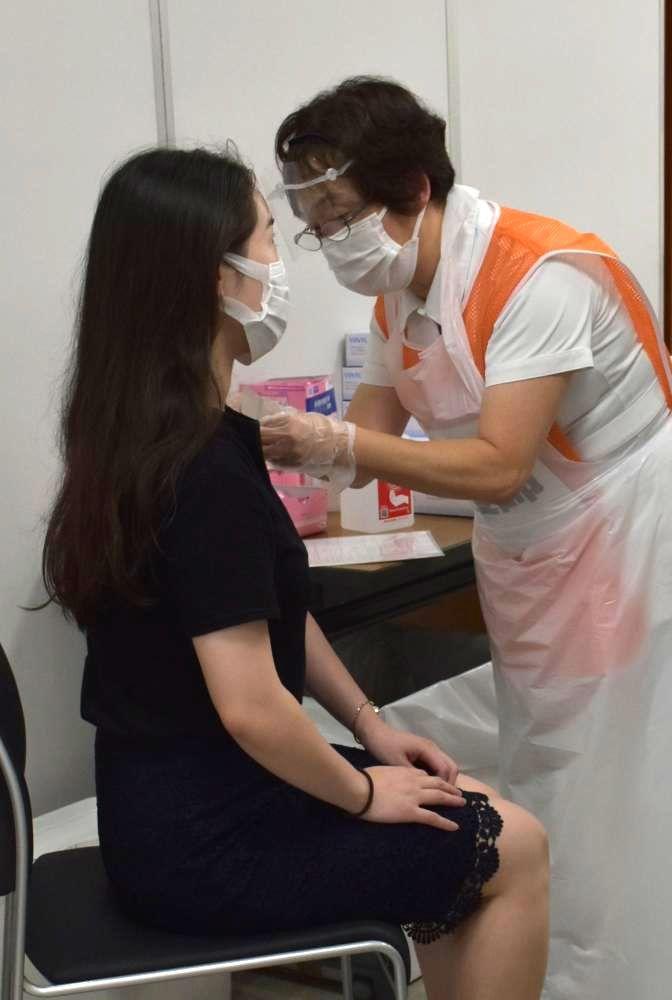 新型コロナウイルスワクチンを打つ常陽銀行の従業員(左)=水戸市南町