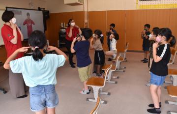 鹿島アントラーズの選手たちが登場する動画(左奥)で英語を学ぶ児童たち=鹿嶋市須賀の市立豊郷小