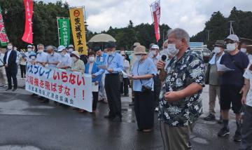 横断幕を掲げ抗議する「百里基地反対連絡協議会」の会員=小美玉市百里