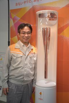 リクシル下妻工場で素材を製造した東京パラリンピックの聖火リレートーチと同工場の西端昭則材料部門長=下妻市大木