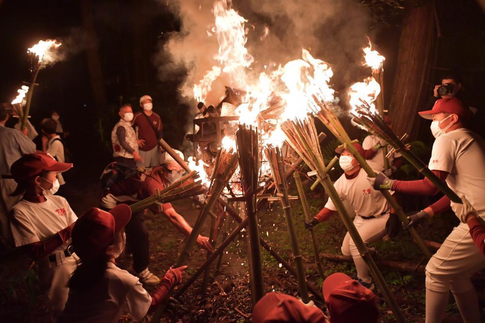 たいまつに移した火を山の入り口まで運ぶ「かったて祭り」の参加者=31日午後6時半ごろ、桜川市真壁町山尾